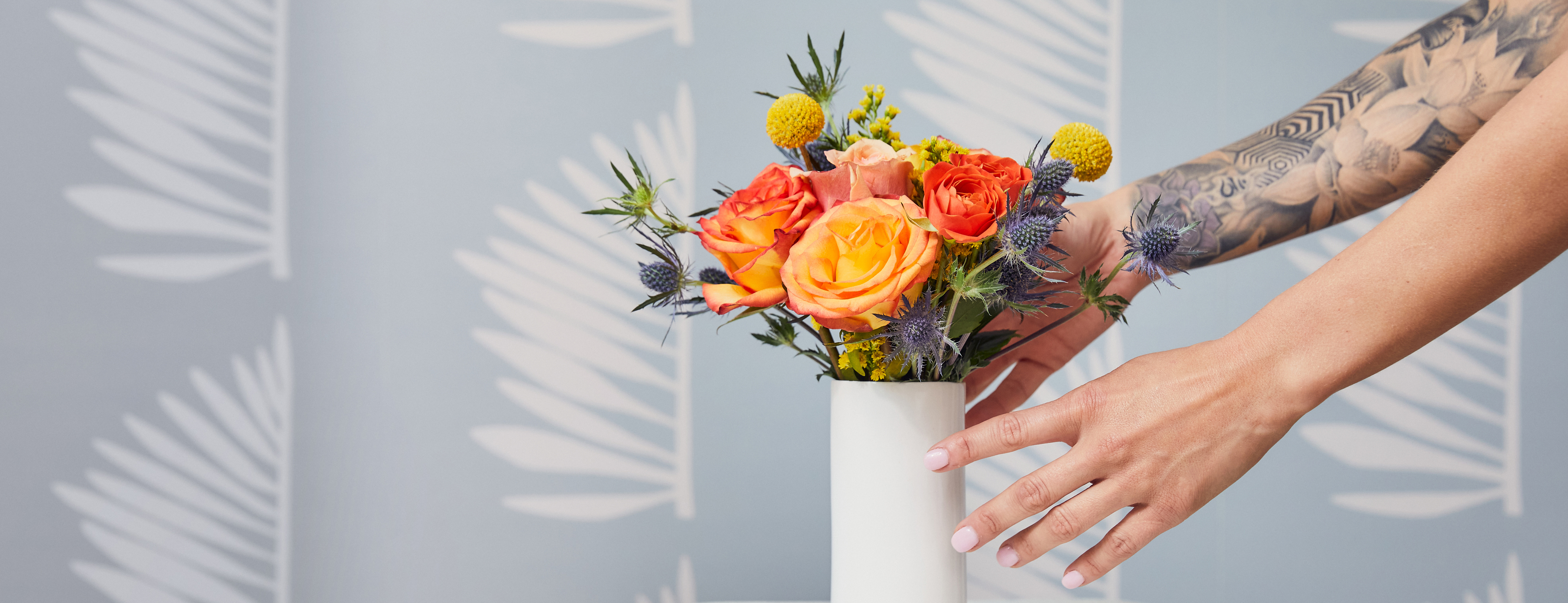 Hands placing a mini flower bouquet in a white vase