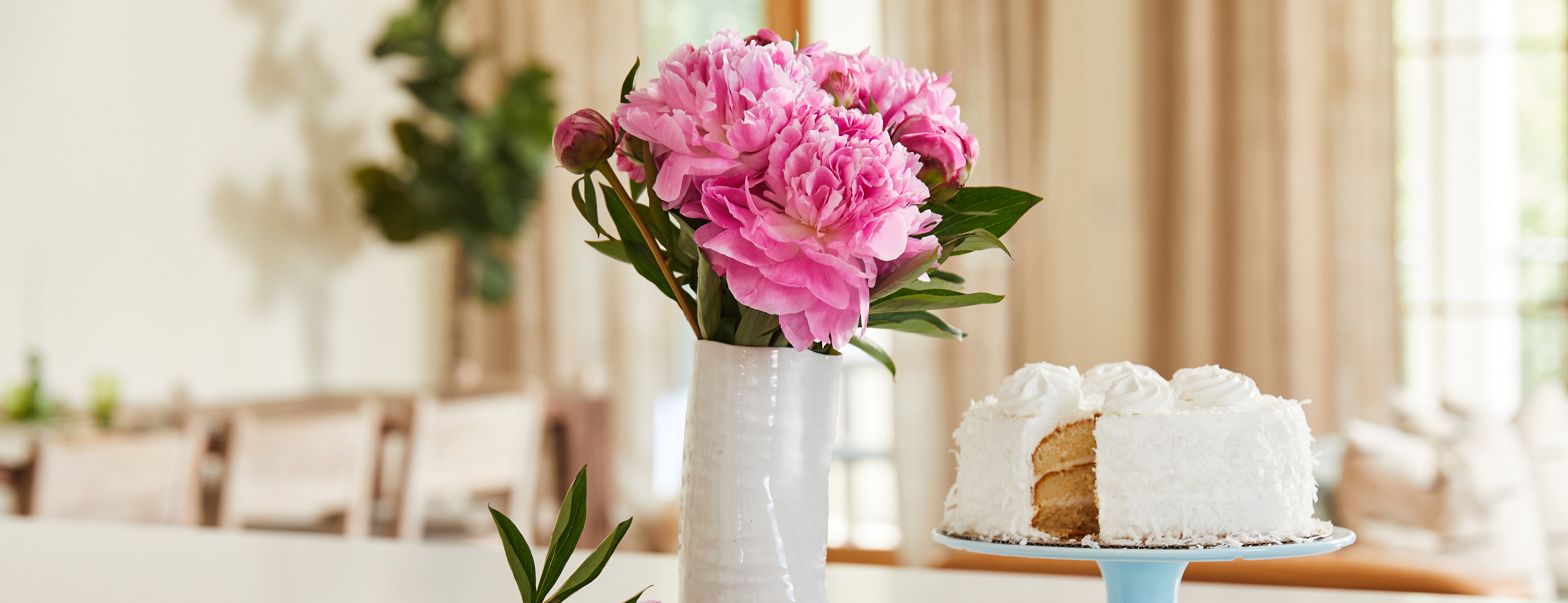 Bouquet of pink flowers in white vase with white birthday cake