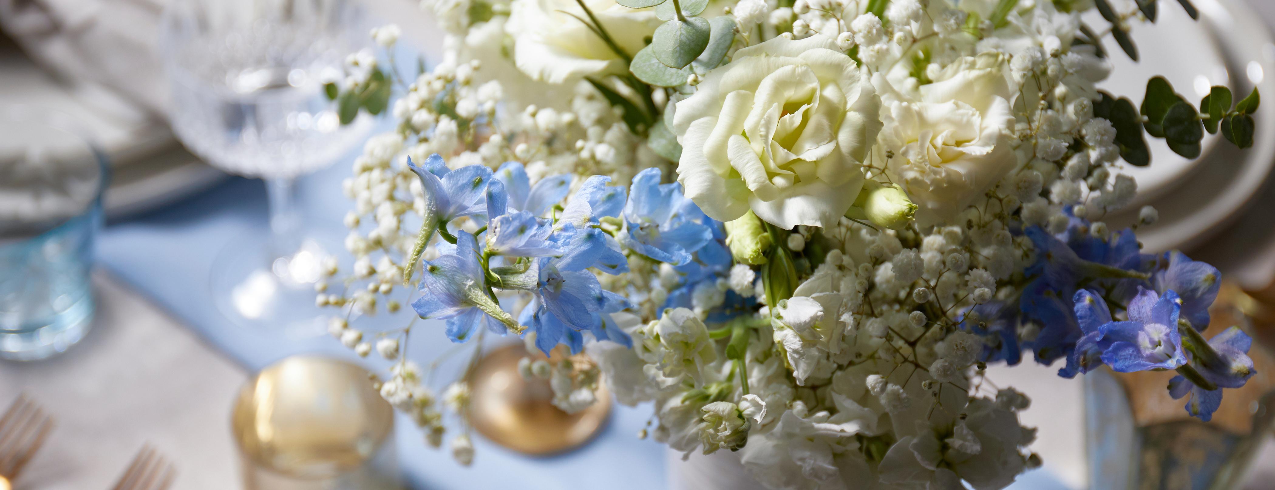 Floral bouquet on set table featuring delphinium flowers