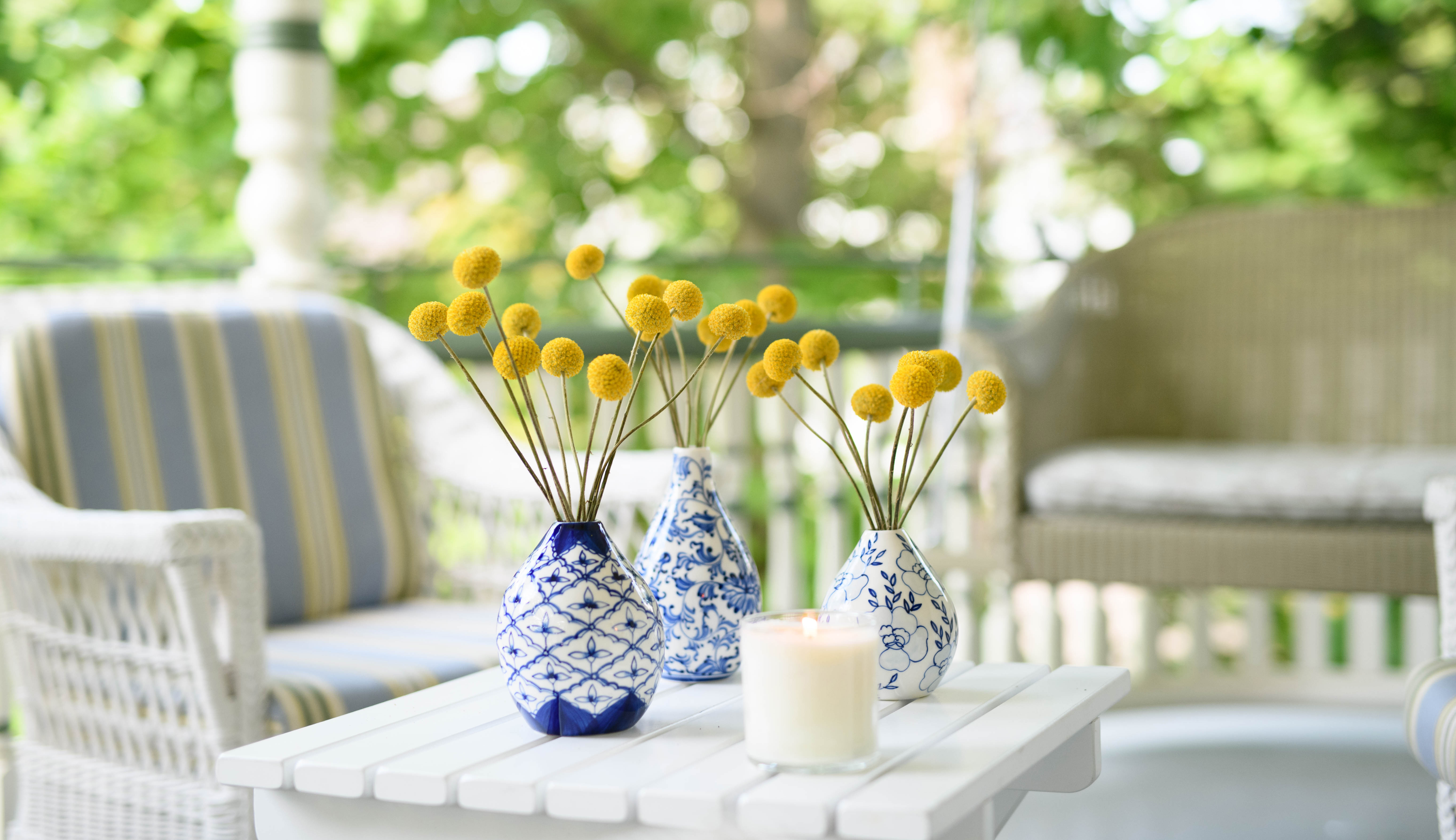 Three blue and white ceramic vases with yellow flowers on an outdoor patio
