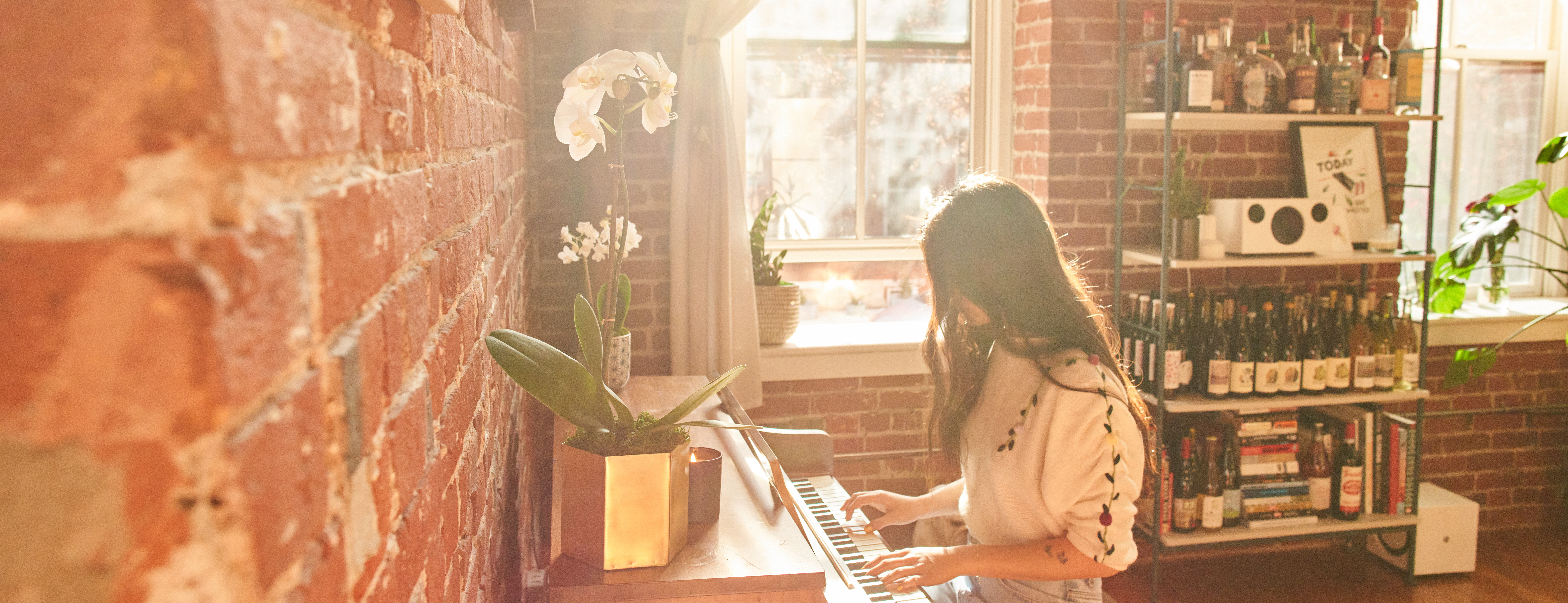 Woman playing piano in the sunlight with two white orchid flowers