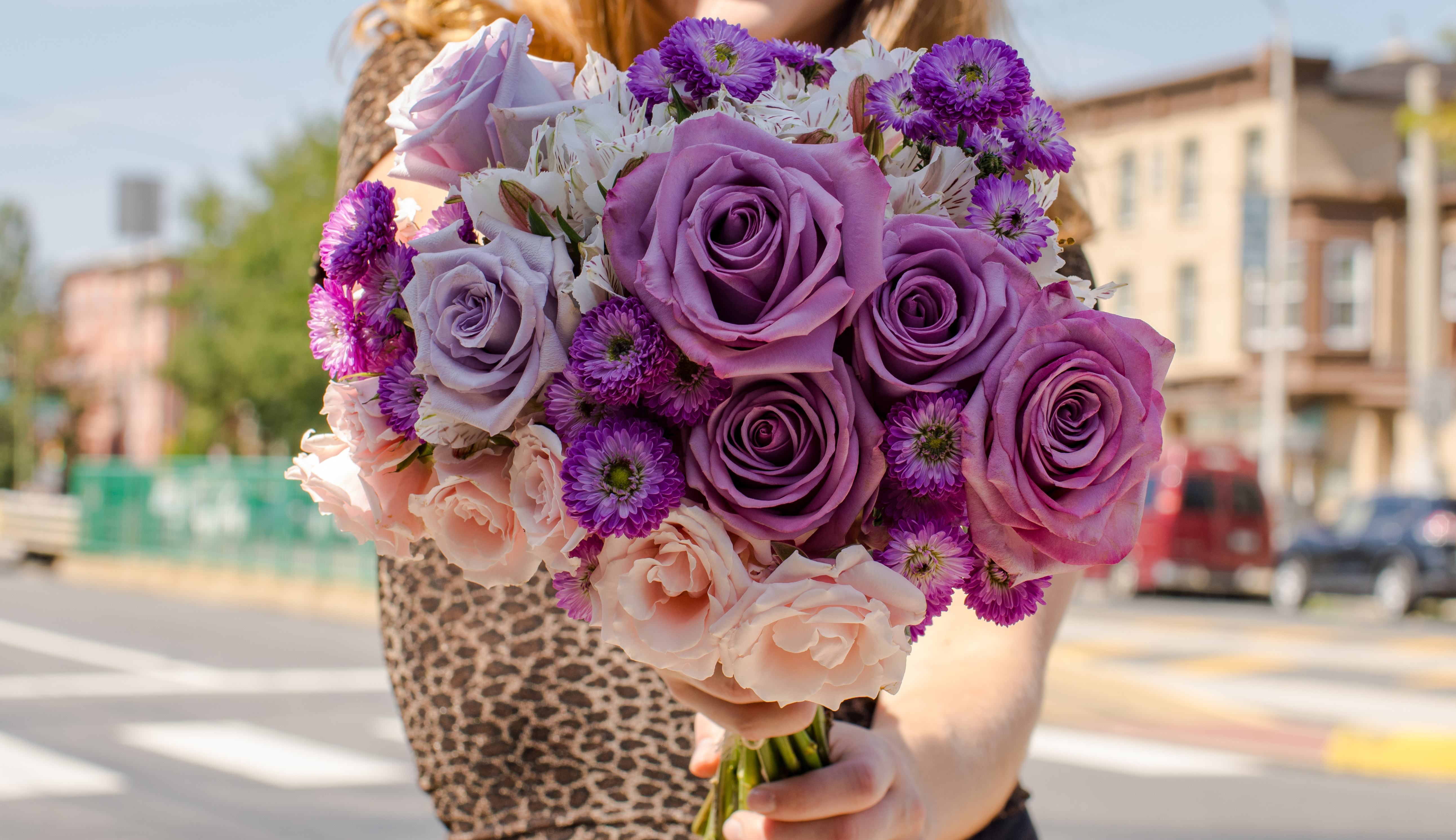 Close up of floral bouquet containing purple asters