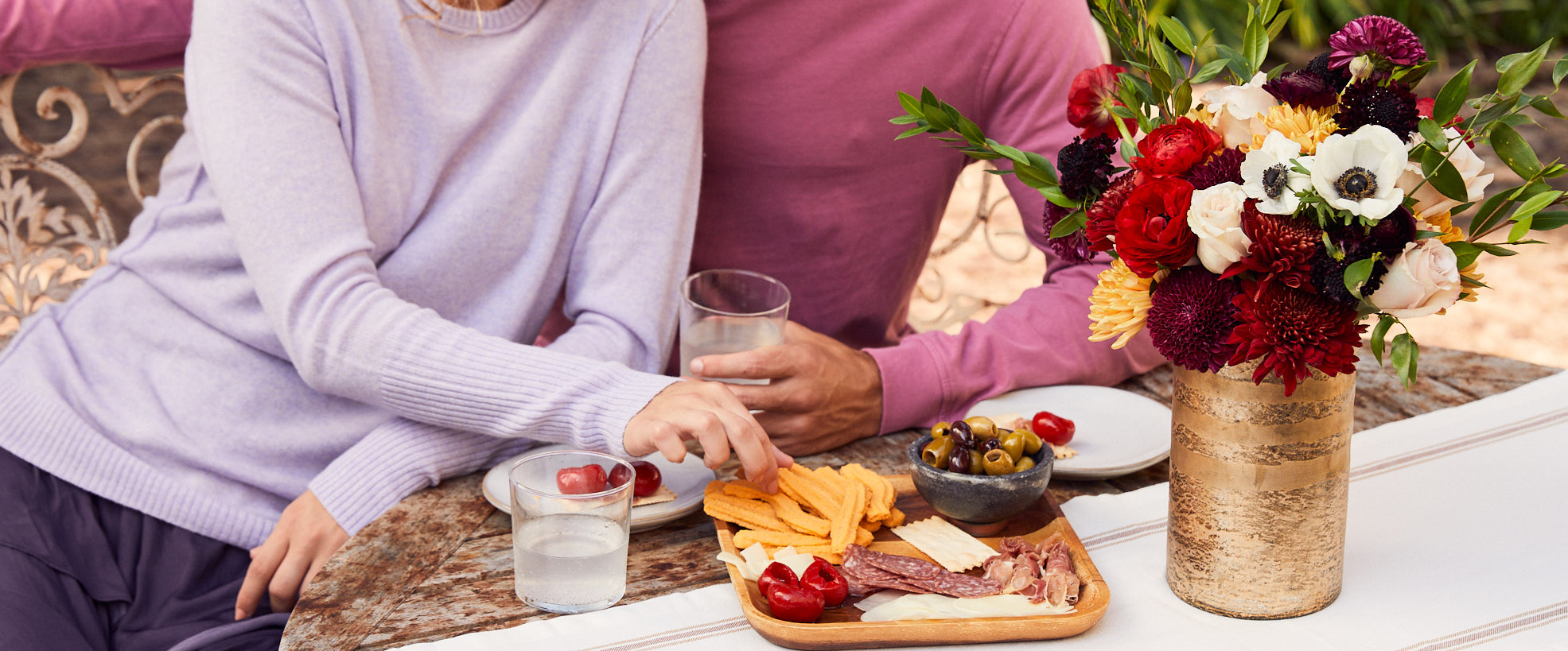 Couple holding an outdoor dinner party for fall with fresh flowers