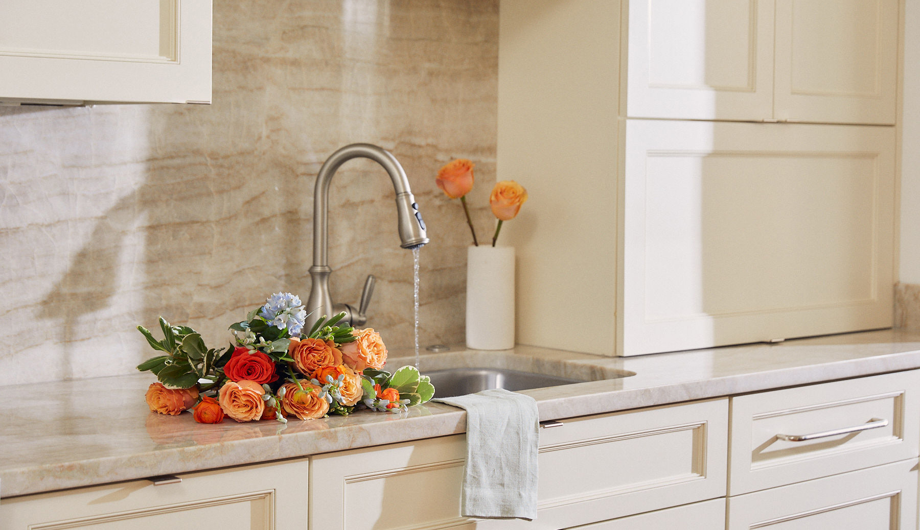 Bouquet of flowers on countertop next to running sink.