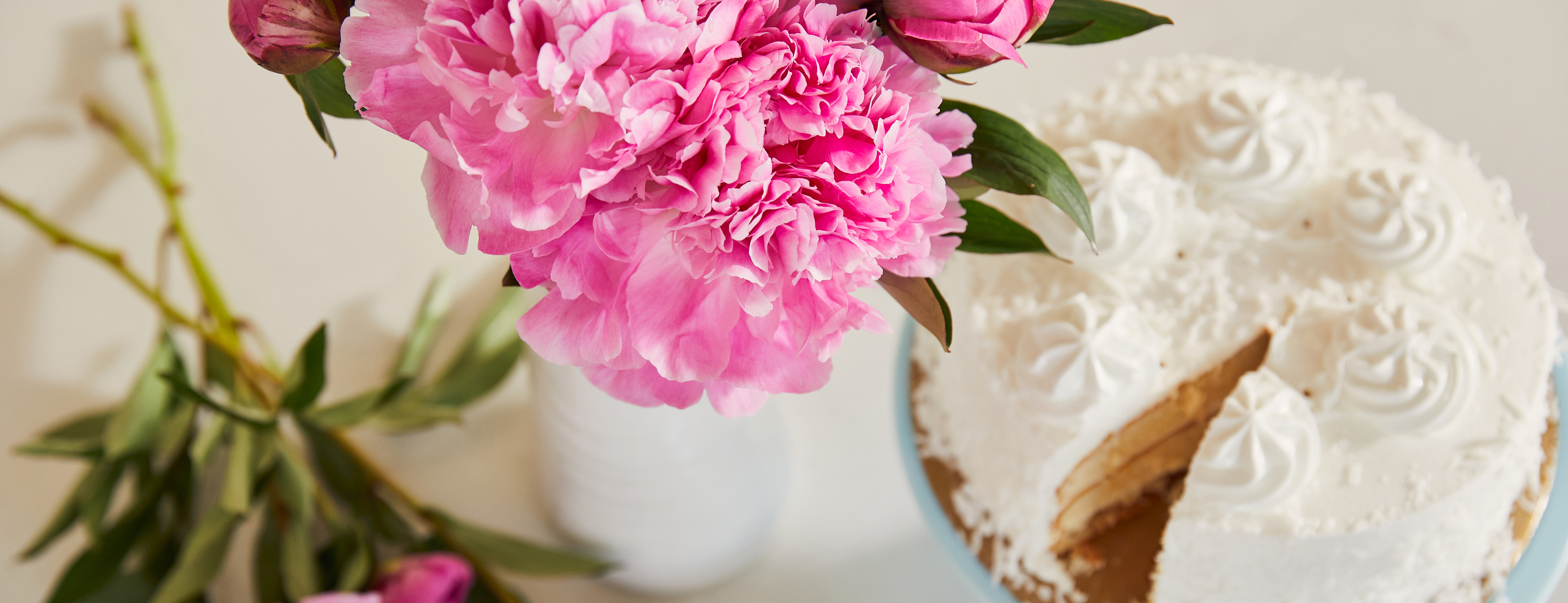 Bouquet of bright pink peonies on a table with frosted white birthday cake.