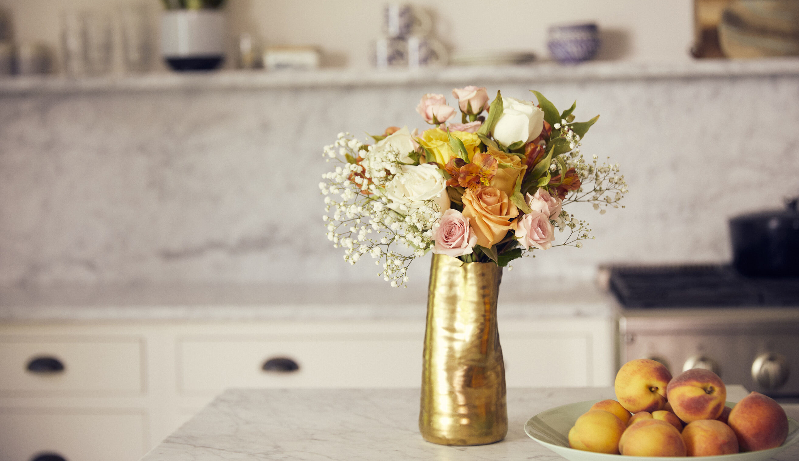 Bouquet of flowers in a gold vase on countertop