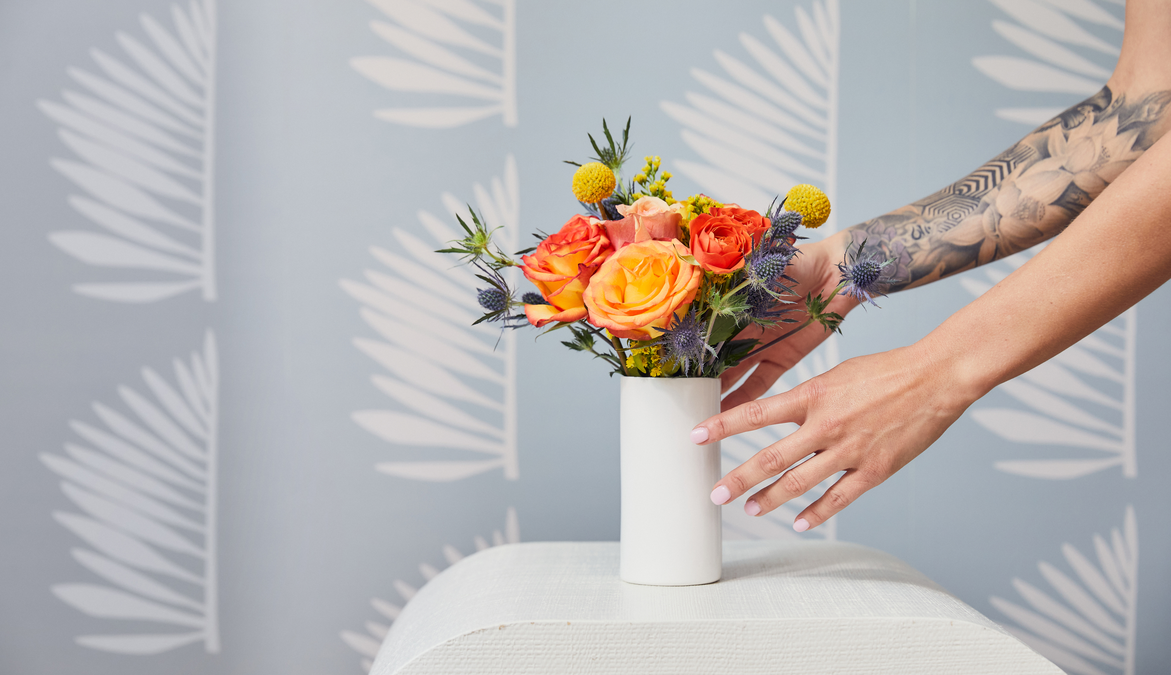 Bouquet of yellow flowers, orange flowers, and blue flowers in white vase