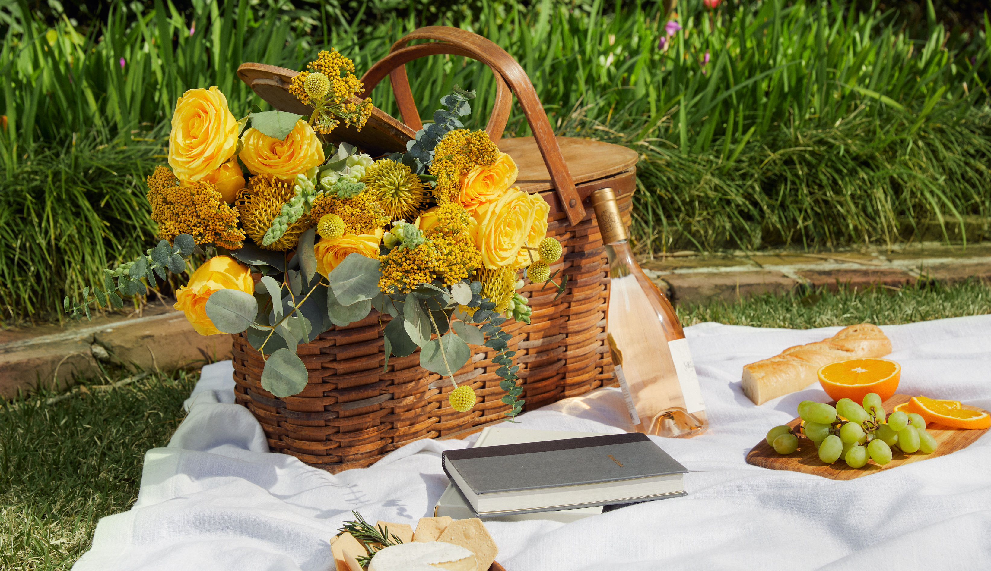 Bouquet of yellow flowers in picnic basket.