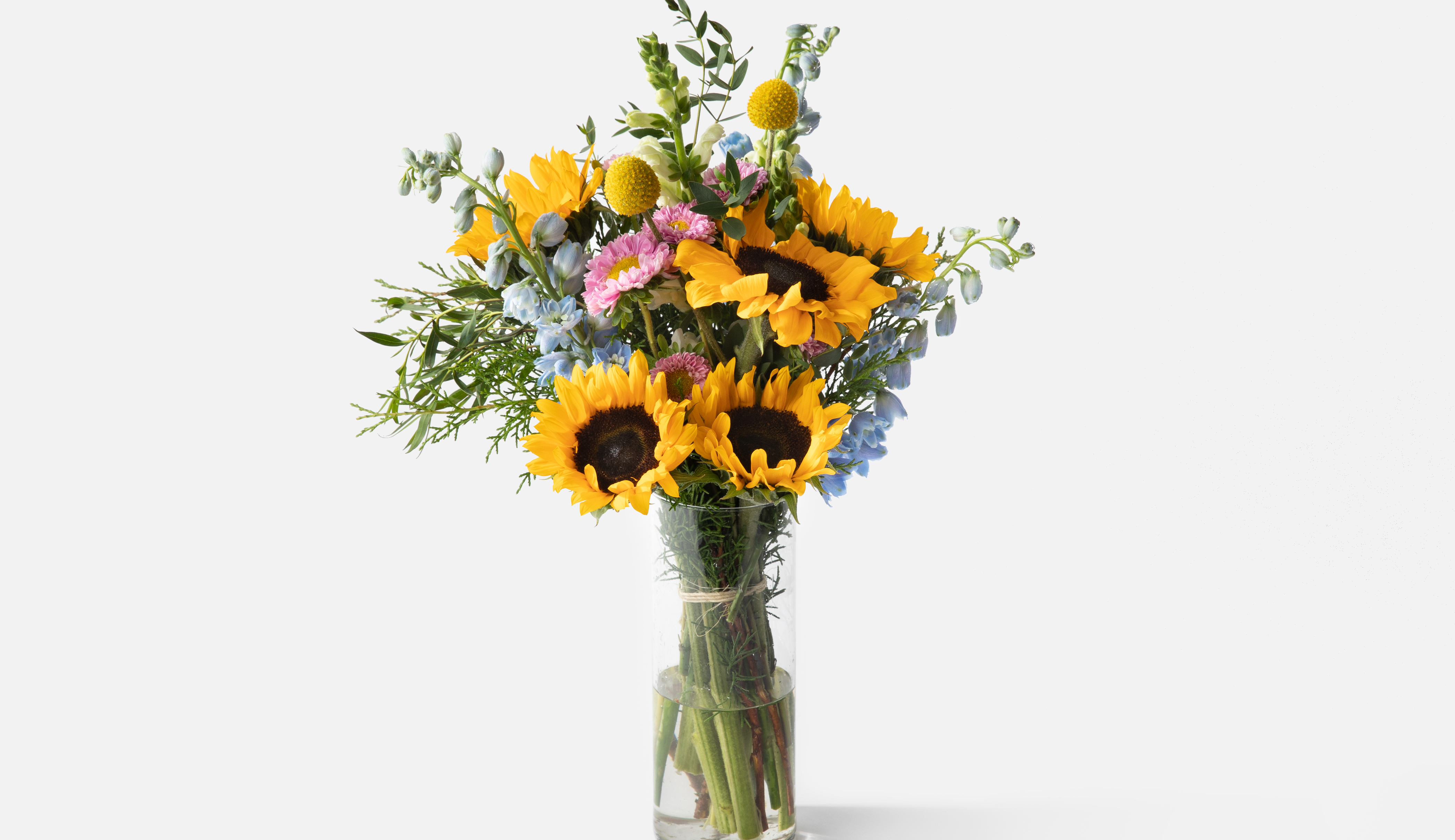 Bouquet with sunflowers and other florals in glass vase.