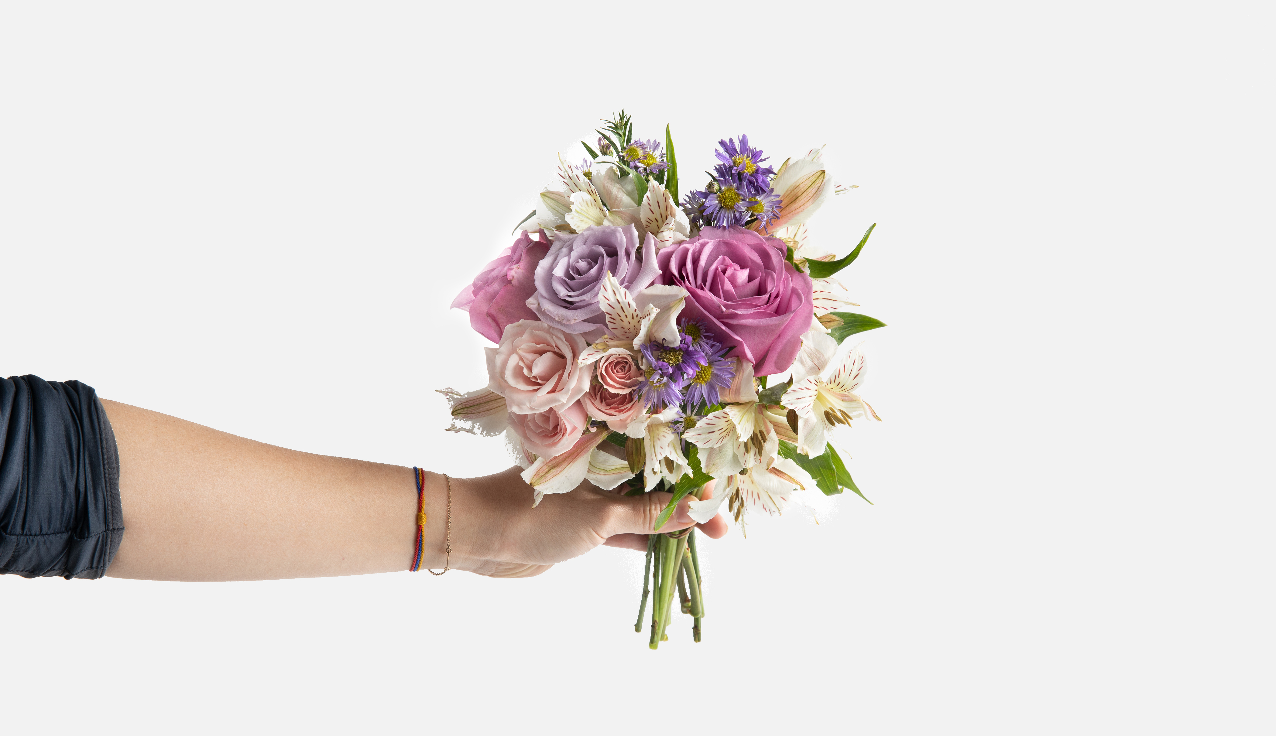 Hand holding mini bouquet of purple and white flowers