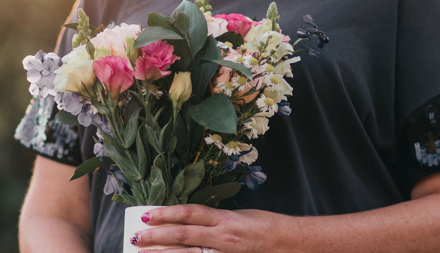Hands holding a vase with a floral bouquet