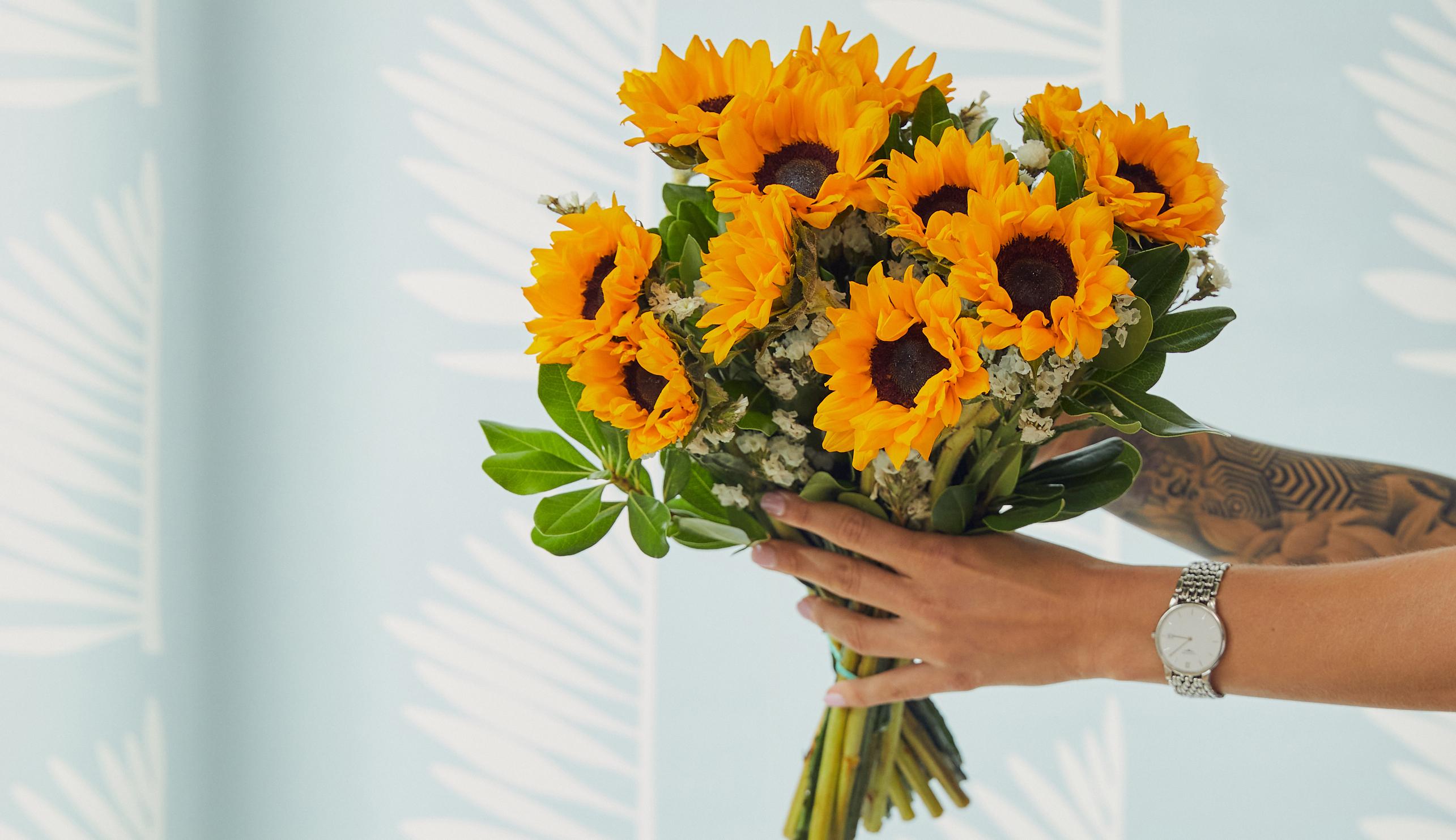 Hands holding sunflower bouquet