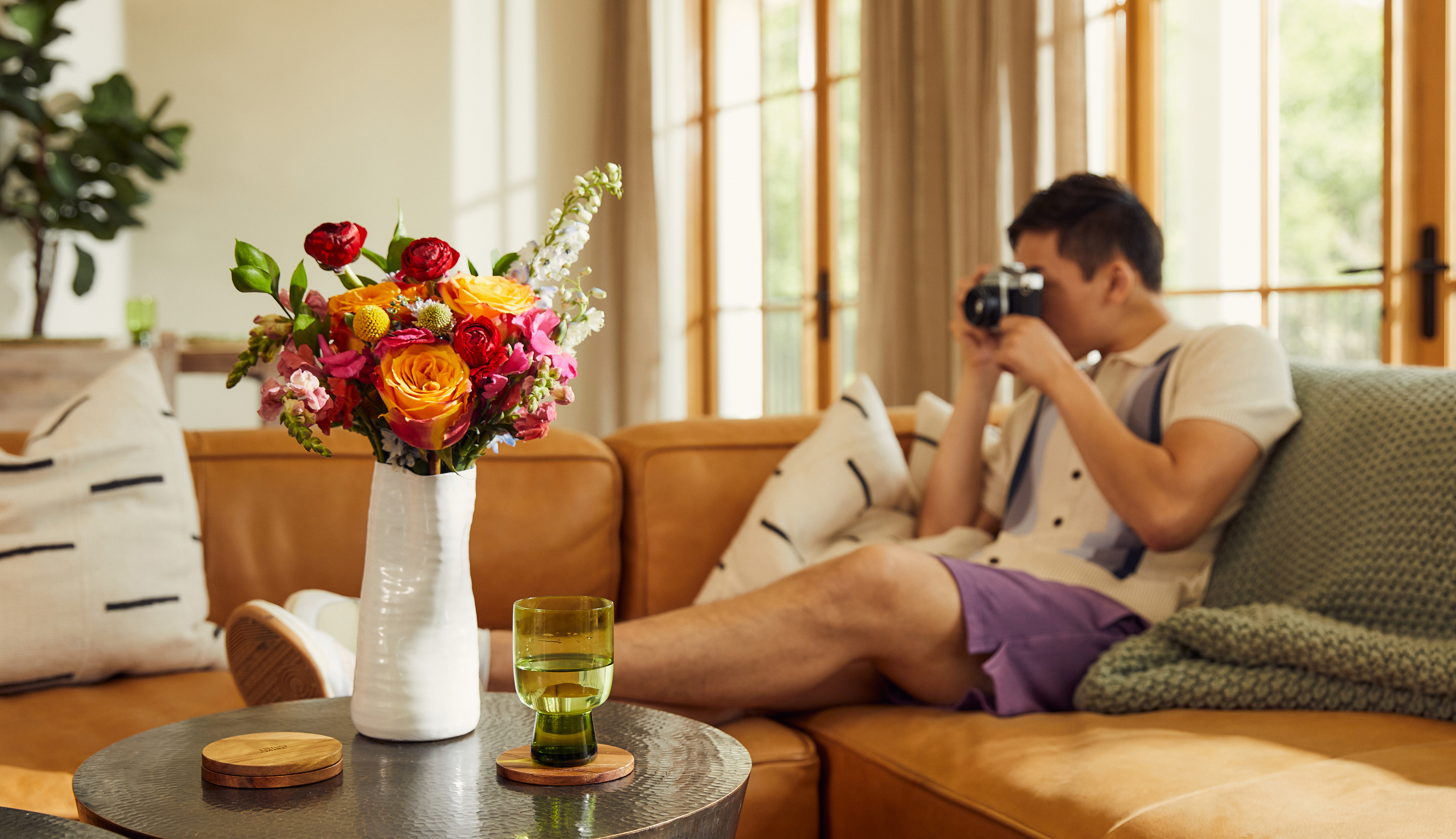 Man relaxing on a couch with a bouquet fo fresh flowers on the coffee table