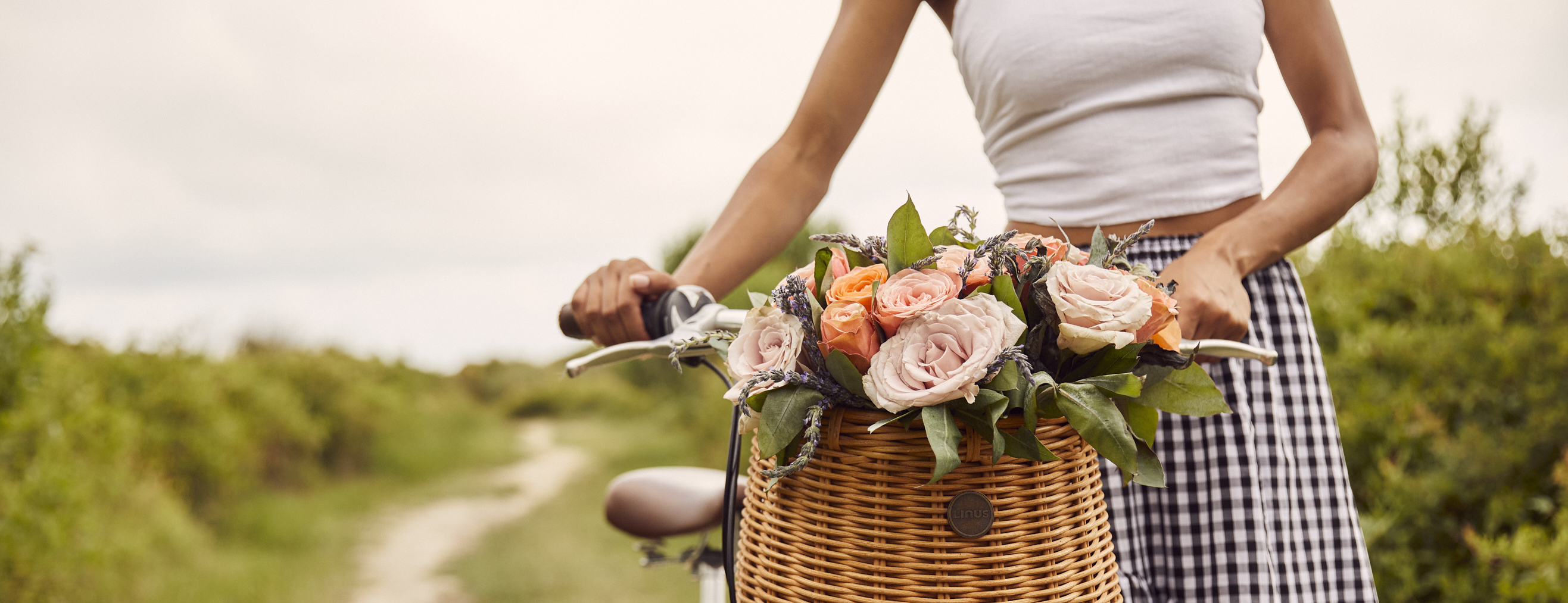 Woman walking a bicycle with a basket full of flowers with a cottagecore aesthetic.