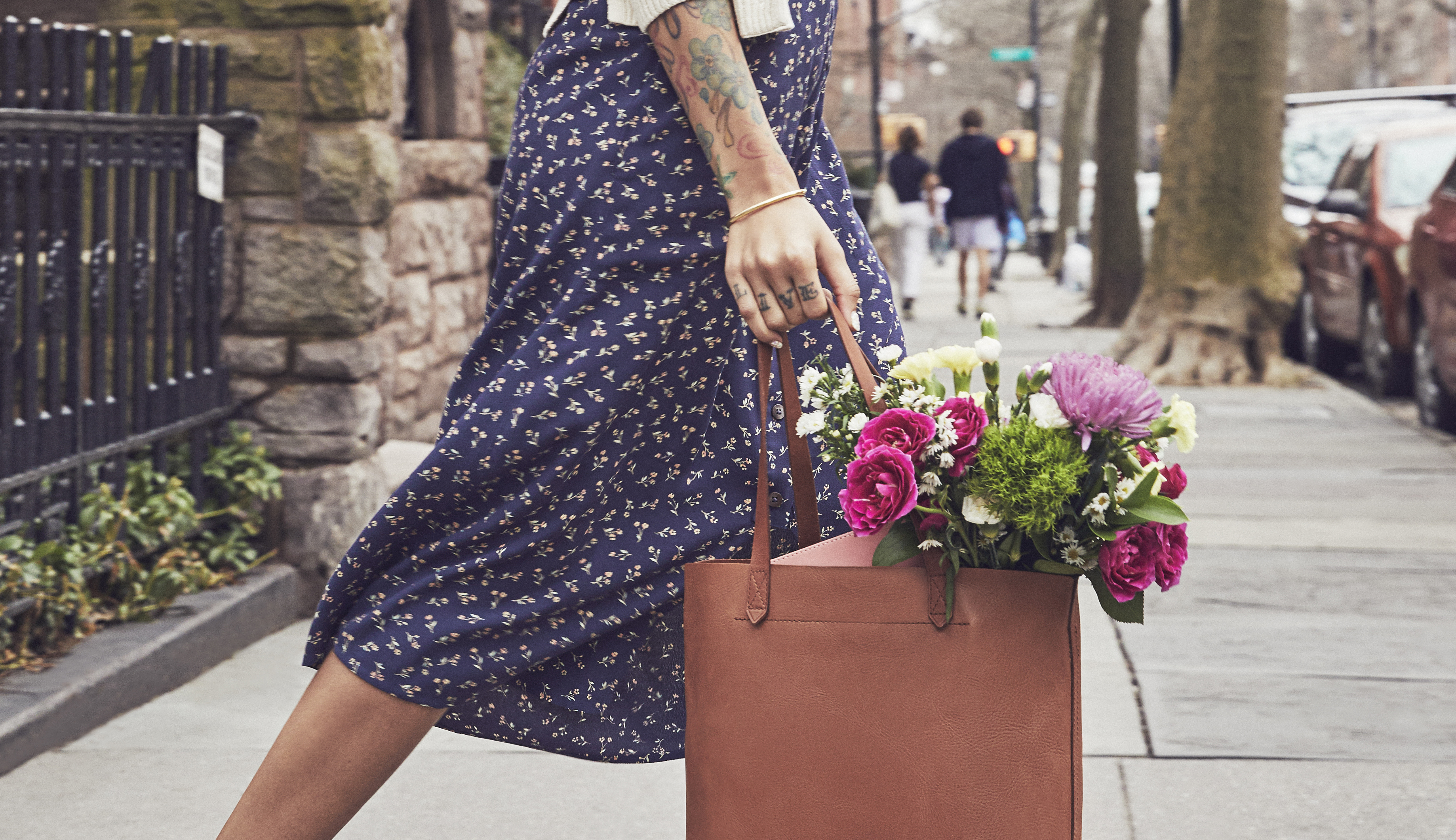 Woman carrying floral bouquet with white asters