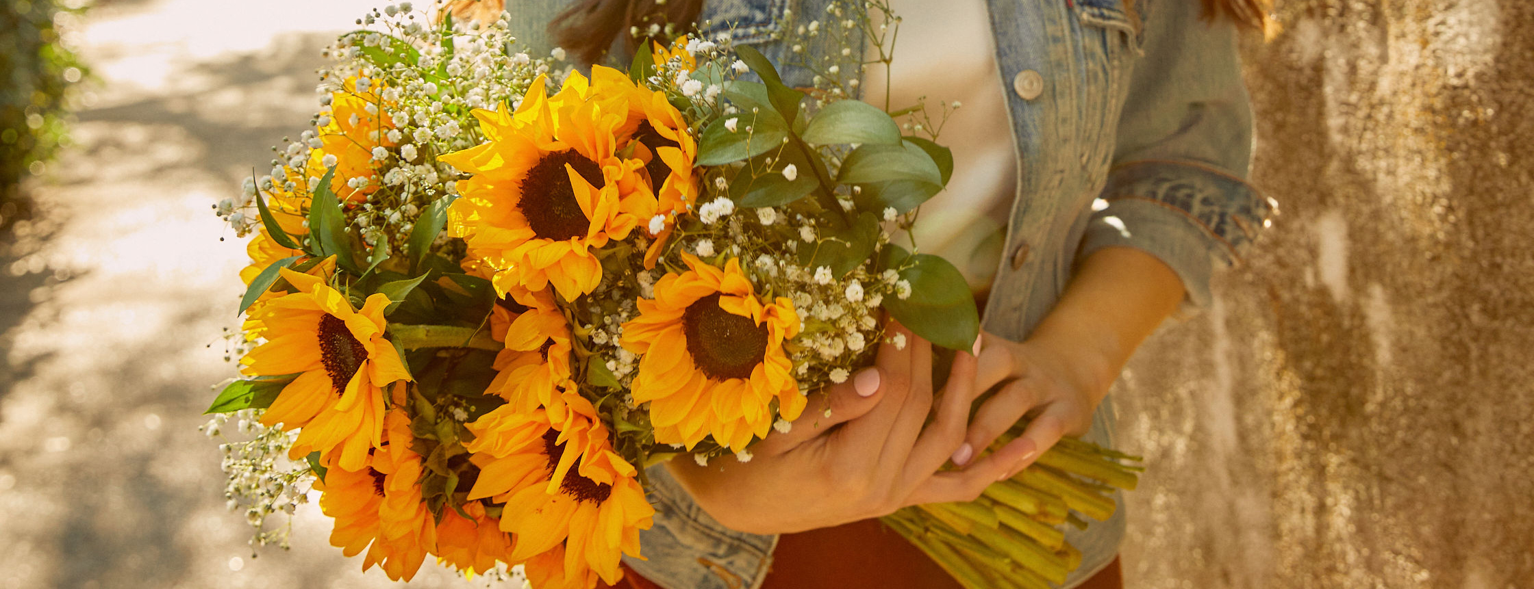 Woman holding sunflower bouquet at golden hour