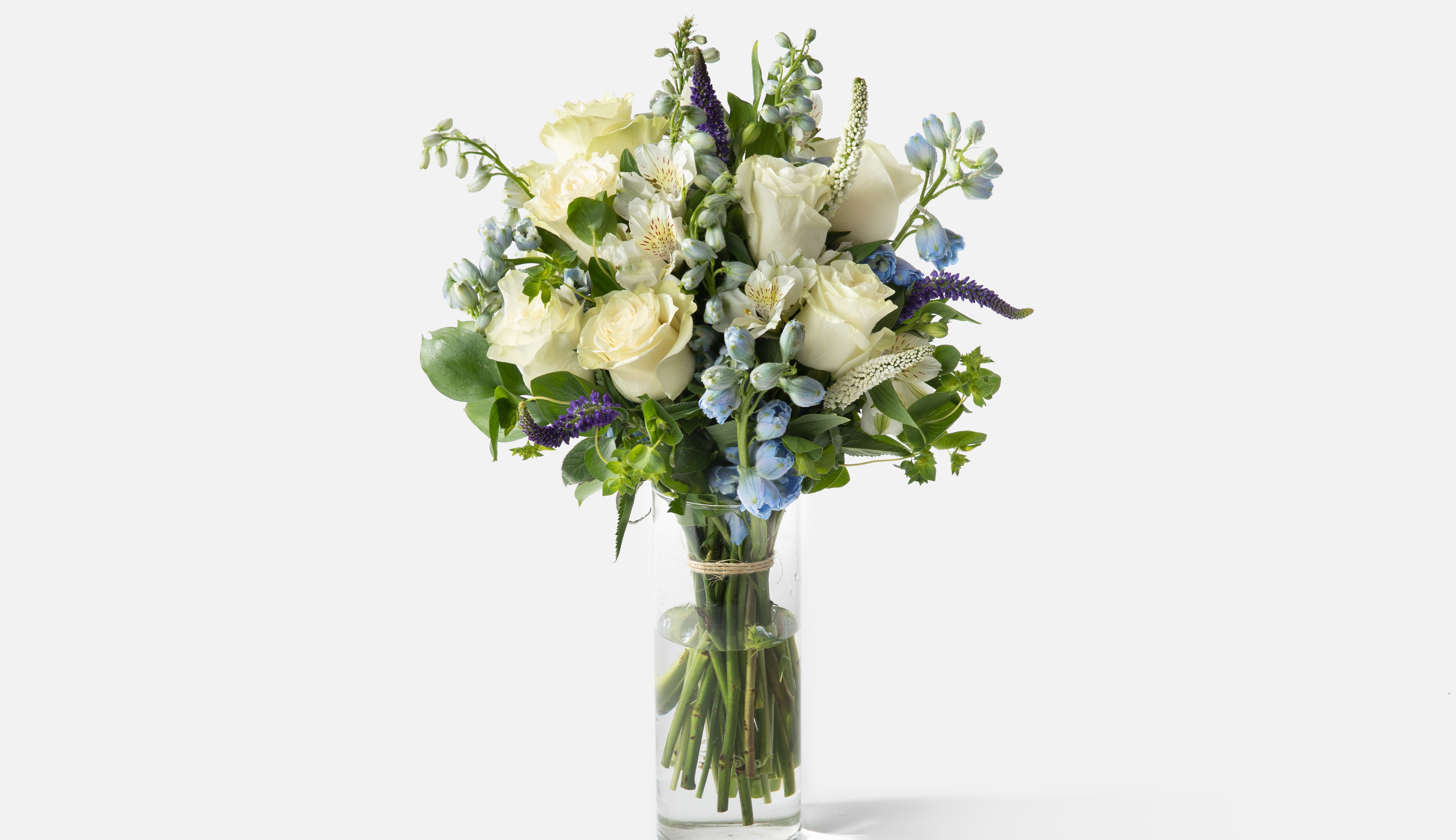 Flower bouquet containing roses and delphiniums in a glass vase