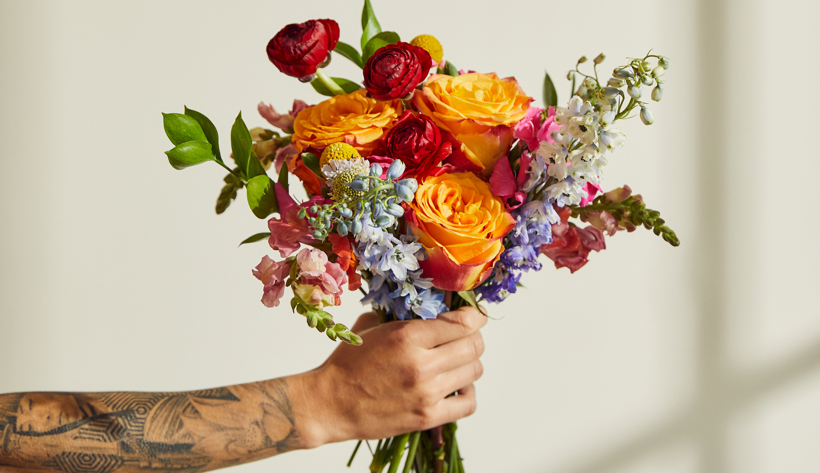 Hand holding rainbow floral bouquet.