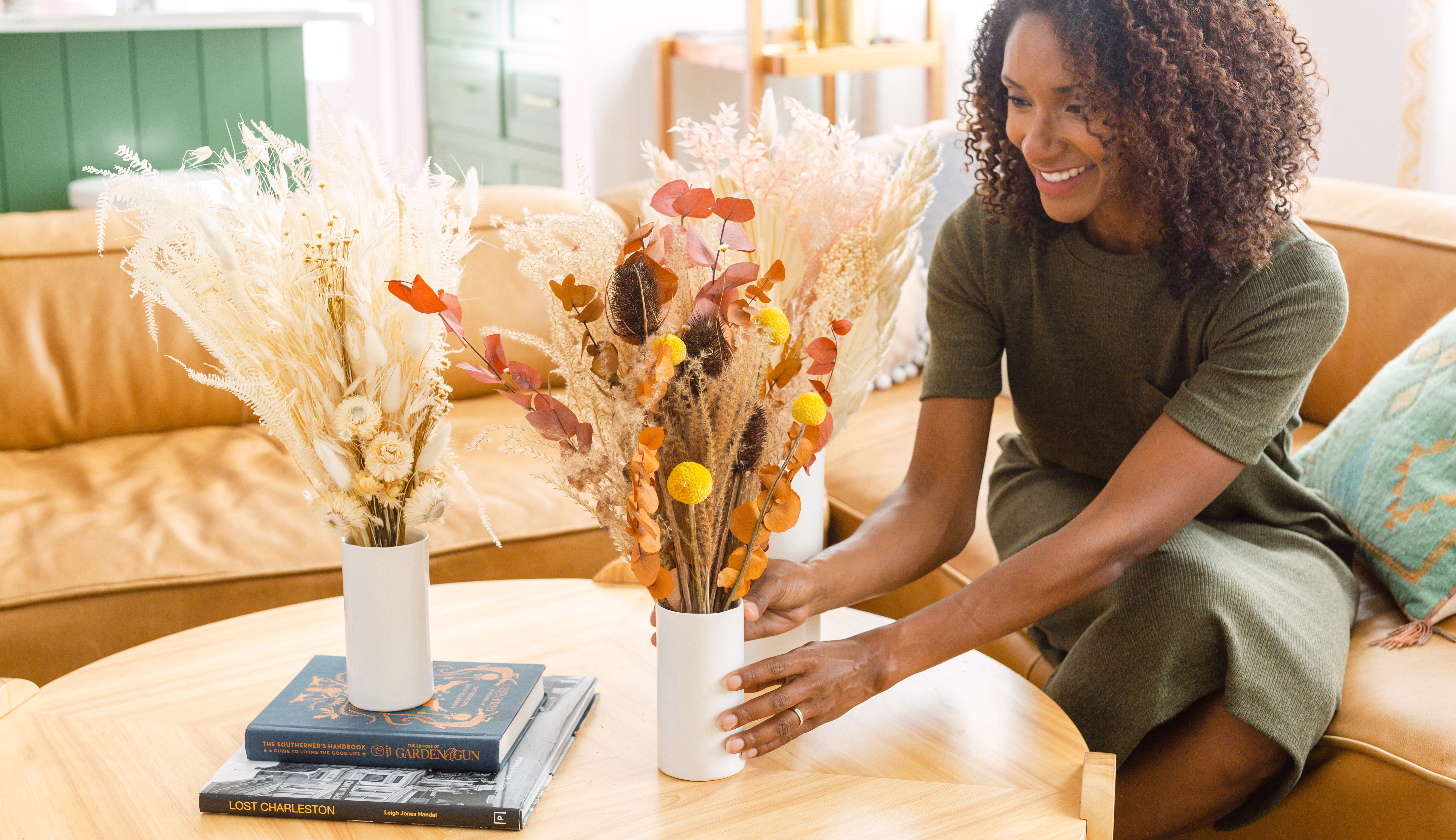 Woman putting three dried floral arrangements on a table