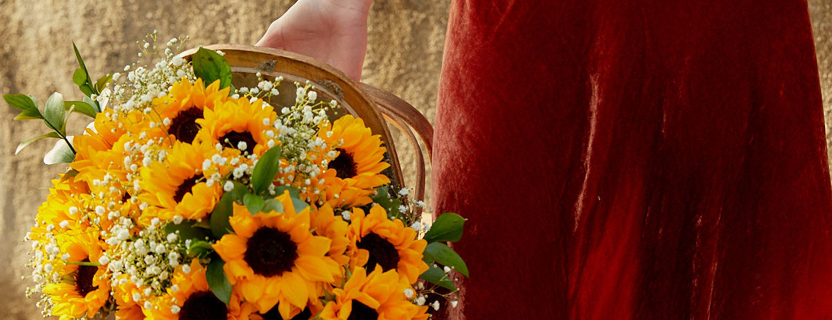 Woman carrying a basket full of sunflowers