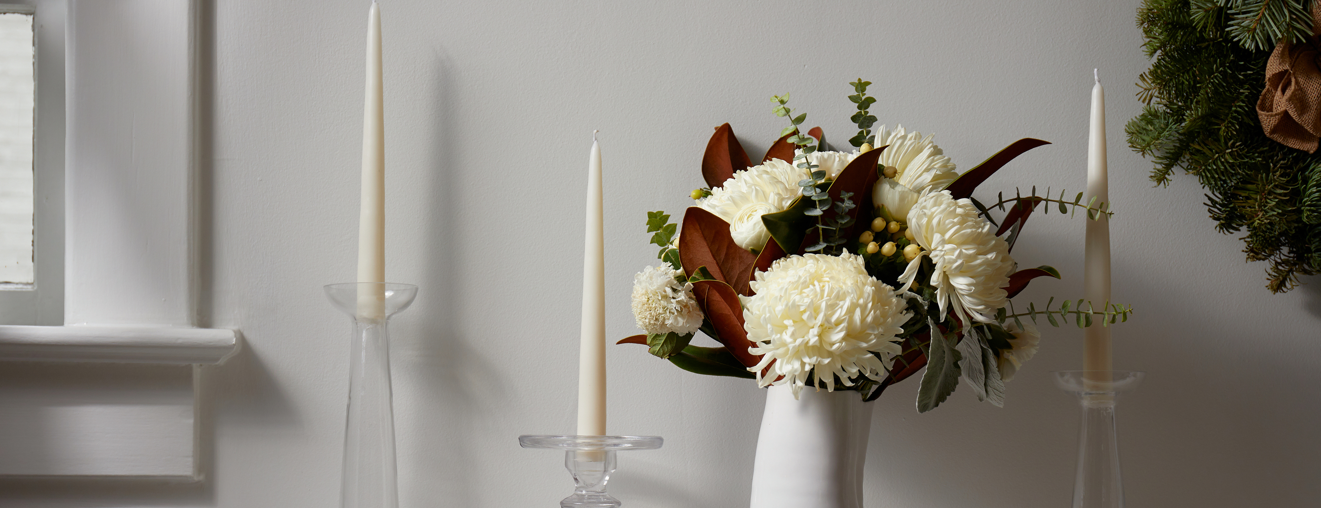 Arrangement with magnolia leaves and tapered candles