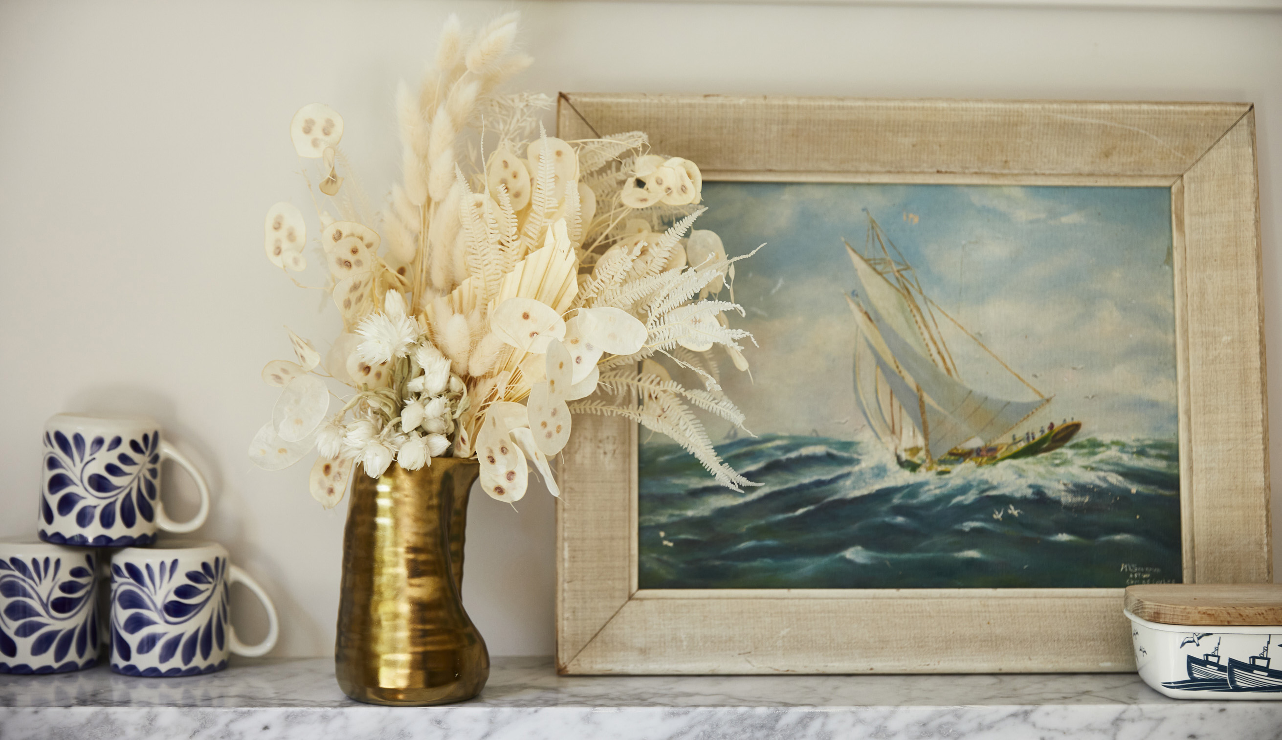 White dried floral arrangement in a gold vase on mantel