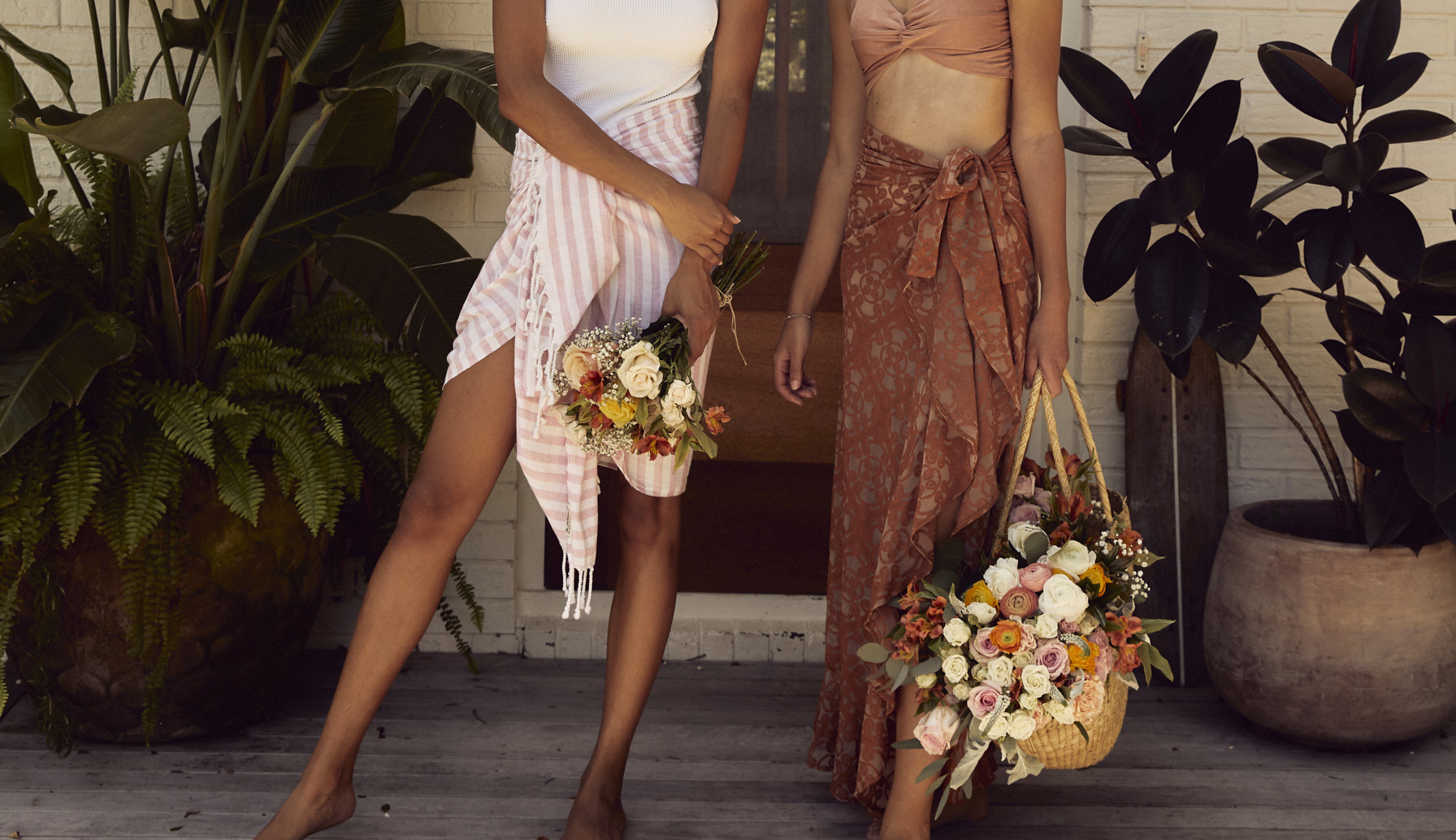 Two women standing on the steps of a beach house each holding a friendship bouquet