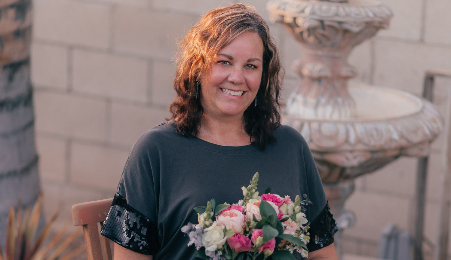 A photo of a woman holding a floral bouquet, the inspiration behind the Breast Cancer Awareness Collection