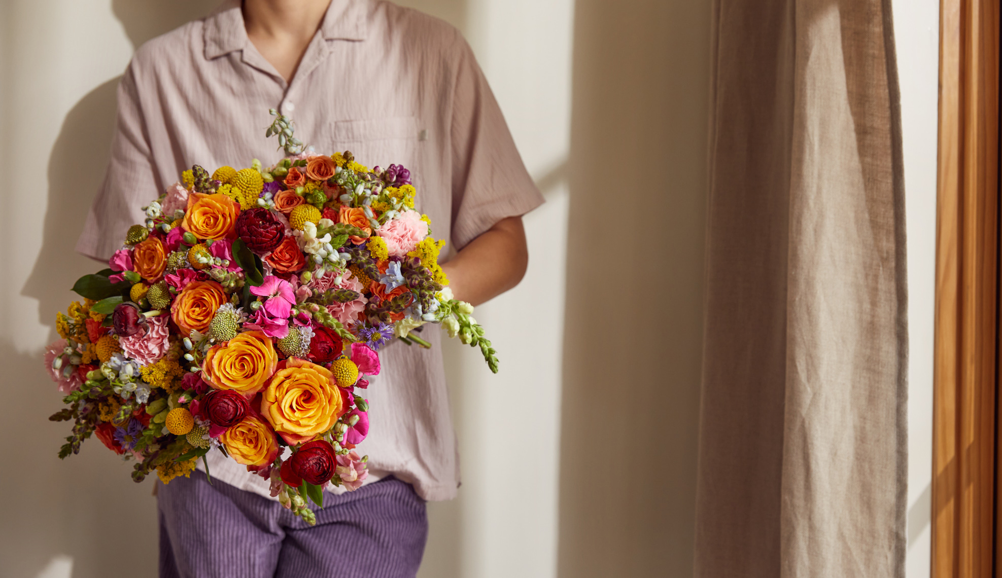 Person in collared light pink shirt with a rainbow flower arrangement.
