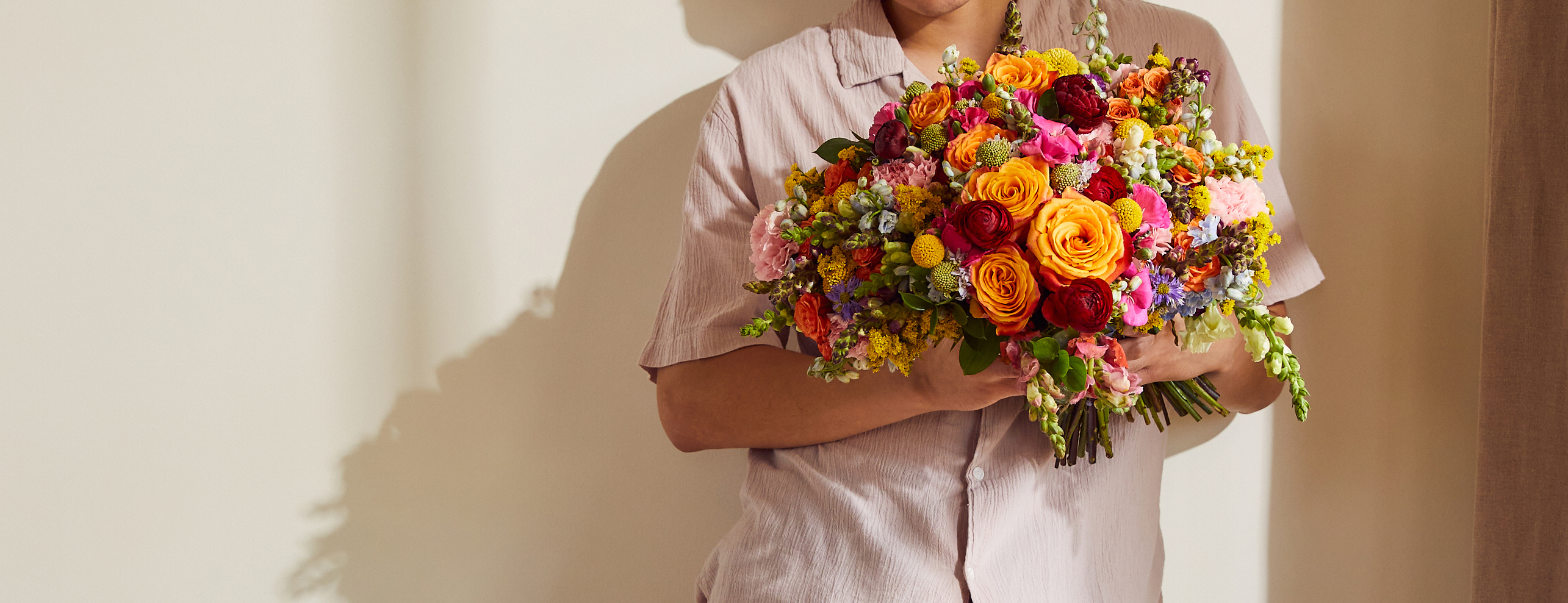 Person holding rainbow flower bouquet