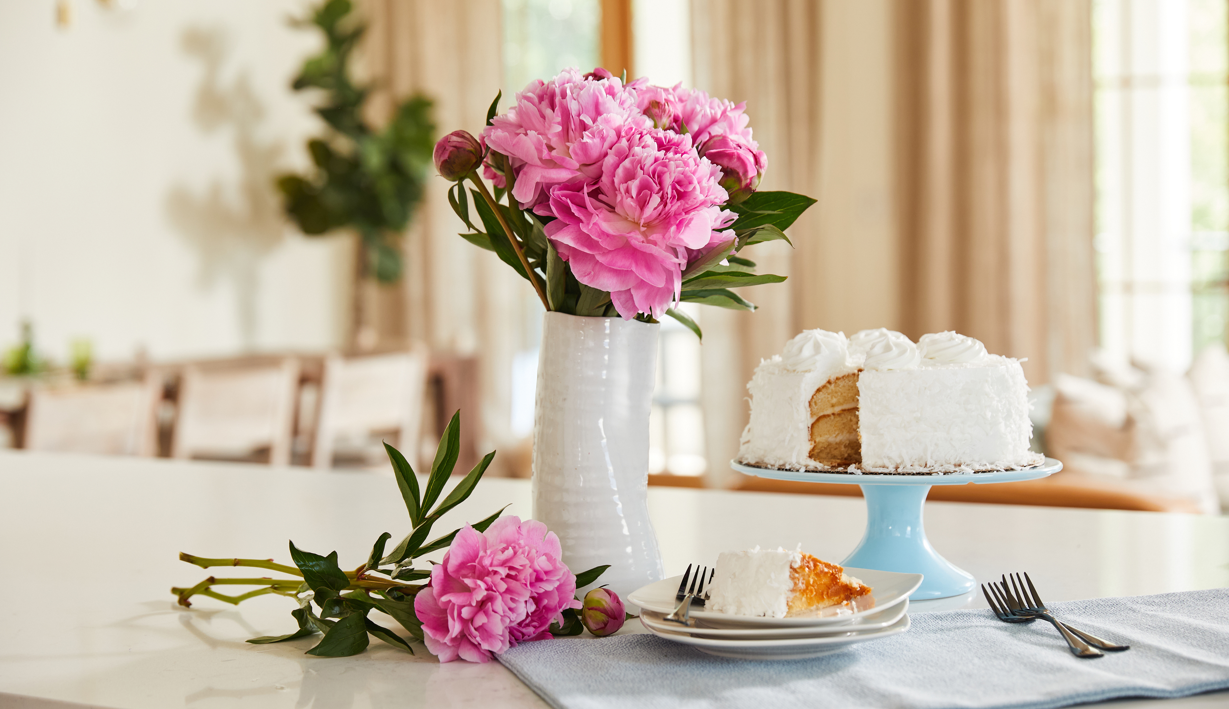 Bouquet of pink peony flowers and white cake on a countertop.