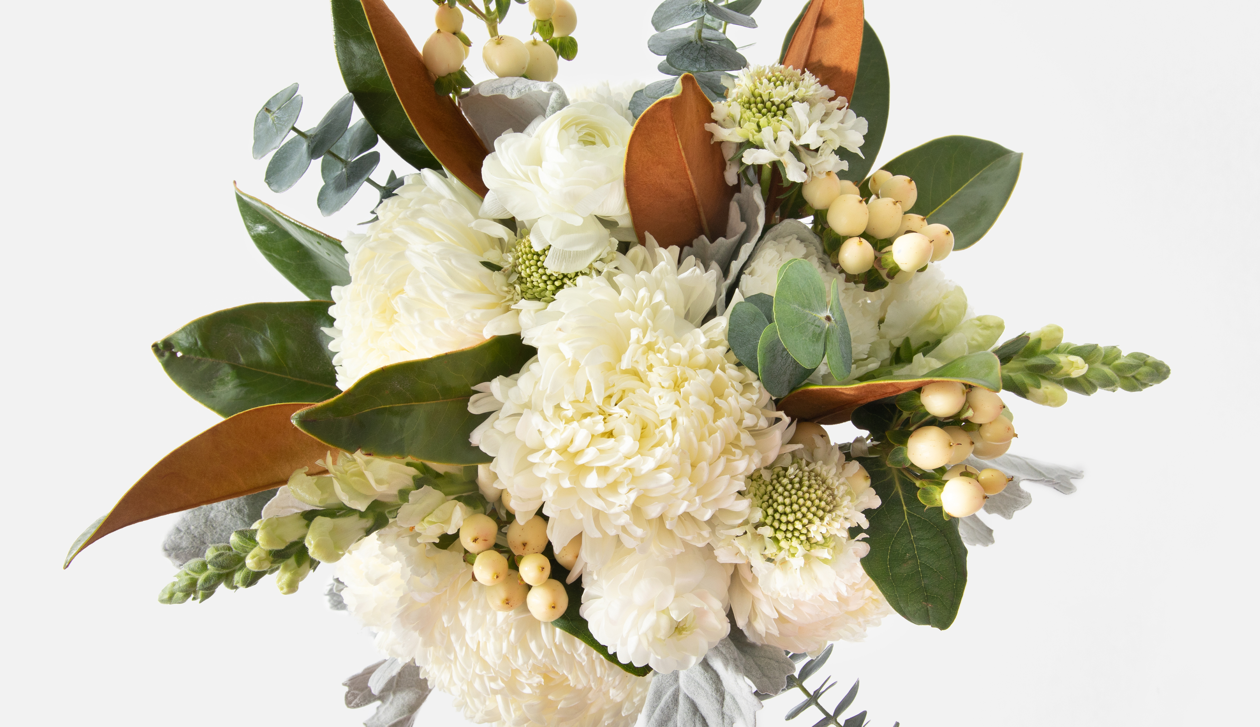 Close up of a floral bouquet containing magnolia leaves