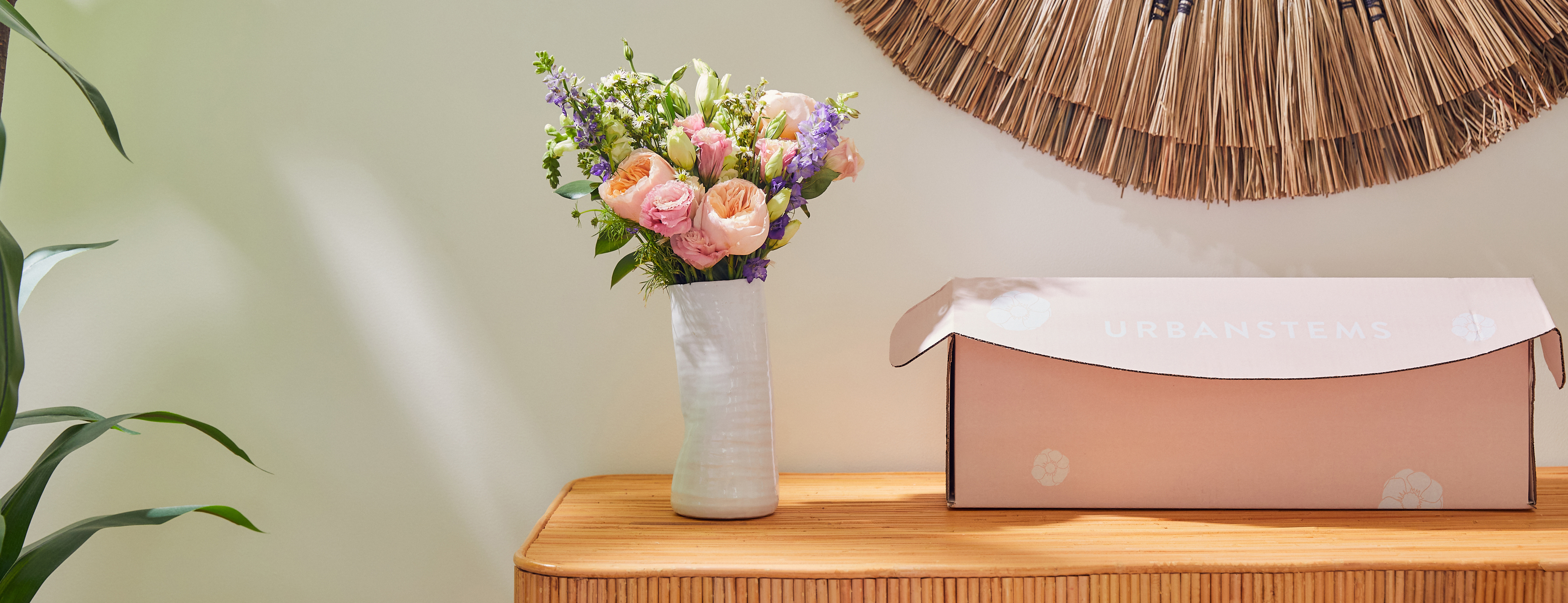 Multicolored flower bouquet and pink box on table.