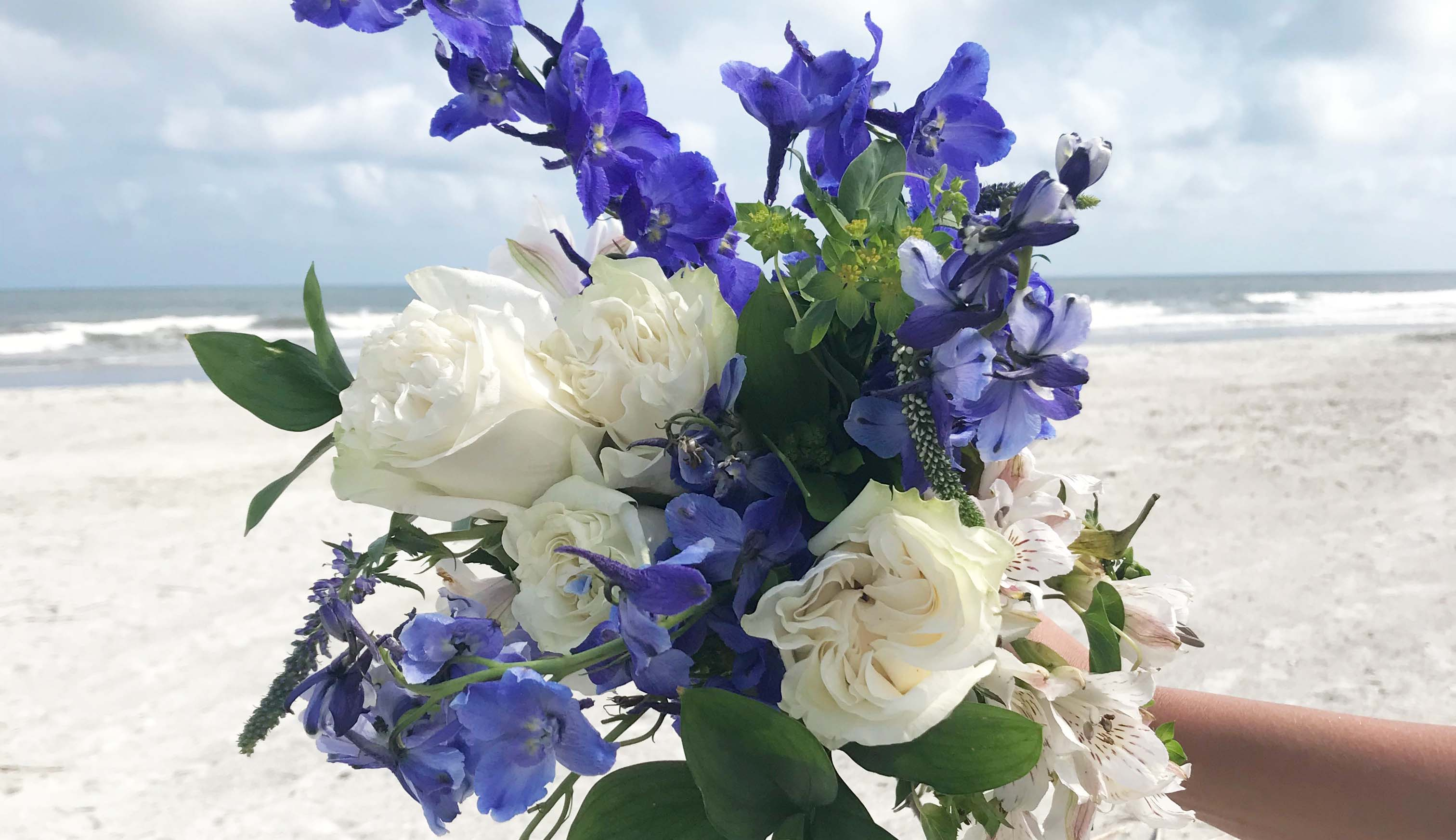 Flower bouquet with delphiniums held on the beach