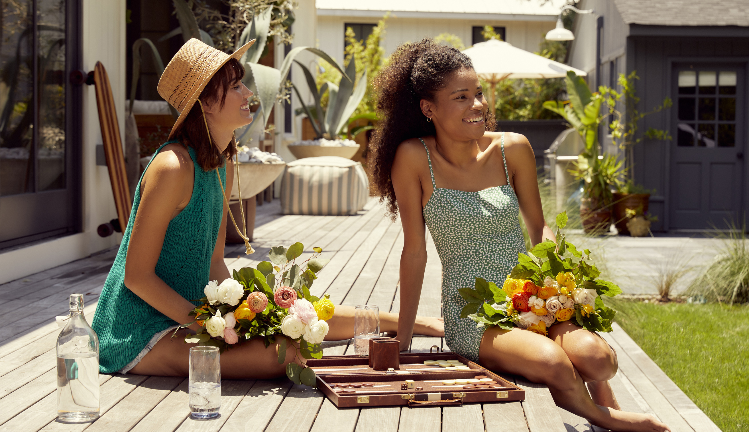 Friends sitting on the deck of a beach house with friendship bouquets