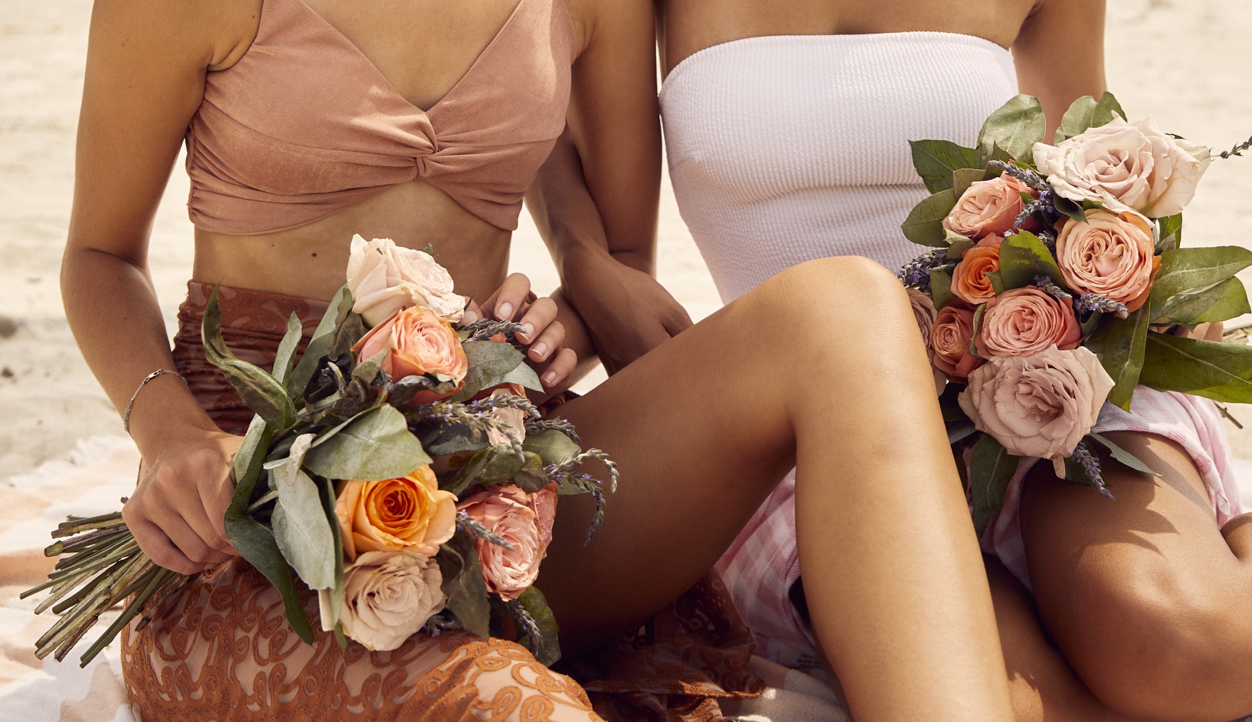 Two women on the beach holding flower bouquets